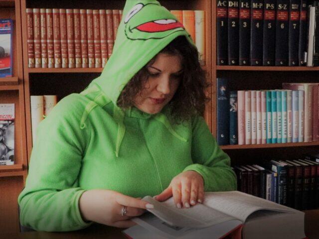 Grafika przedstawia dziewczynę w stroju żaby, która czyta książkę