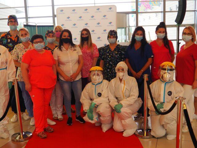 Na zdjęciu osoby w różnorodnych strojach pielęgniarskich oraz kombinezonach covidowych