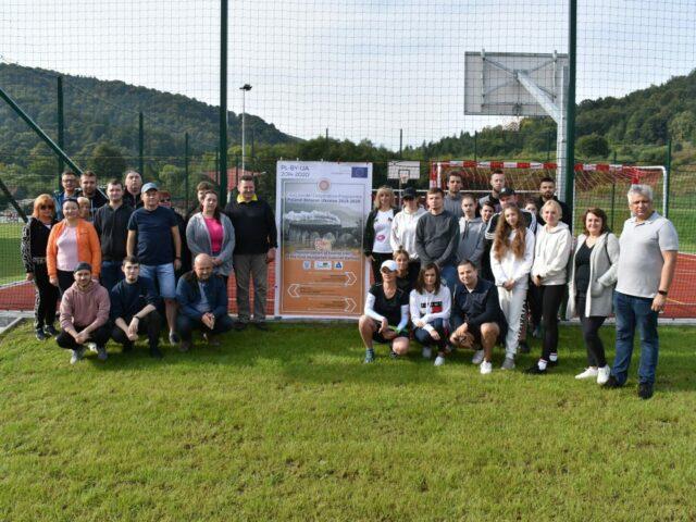 Studenci i wykładowcy PWSW na tle rollupu projektowego na boisku sportowym podczas wycieczki turystyczno-krajoznawcza śladami dawnej galicyjskiej linii kolejowej z Przemyśla do Budapesztu